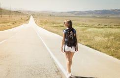 Backpacker женщины идя на дорогу Стоковое Фото
