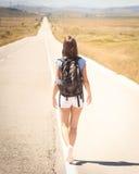 Backpacker женщины идя на дорогу Стоковая Фотография