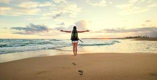Backpacker женщины приветствуя заход солнца на побережье океана Стоковое Фото