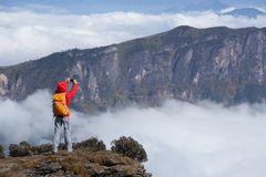 Backpacker женщины принимая selfie на крае скалы горного пика Стоковая Фотография RF