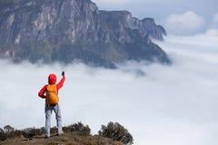 Backpacker женщины принимая selfie на крае скалы горного пика Стоковое Изображение RF