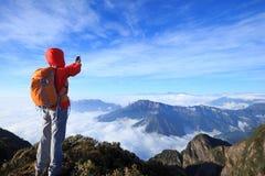 Backpacker женщины принимая selfie на крае скалы горного пика Стоковое Фото