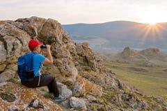 Backpacker женщины смотрит ландшафт через бинокли Стоковые Изображения
