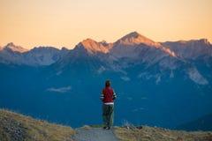 Backpacker идя на тропу в горе Лето рискует летние каникулы на Альпах Люди Wanderlust путешествуя жулик стоковое фото rf