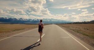 Backpacker молодой женщины идя на дорогу сток-видео