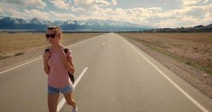 Backpacker молодой женщины идя на дорогу акции видеоматериалы