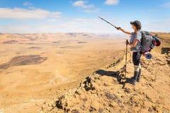 Backpacker молодой женщины туристский стоя смотрящ край горы пустыни взгляда стоковые фотографии rf