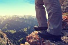 Backpacker на скале горного пика Стоковая Фотография