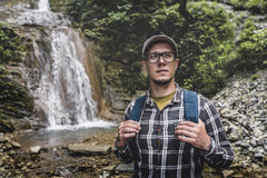 Backpacker стоя и смотря вверх около концепции назначения перемещения путешествием водопада Стоковое Изображение