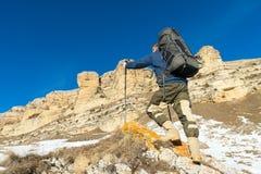 Backpacker с большим рюкзаком и ручками восходит к утесу на фоне былинных утесов в зиме Стоковые Фото