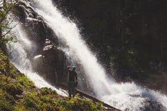 Backpacker человека Hikers смотря водопад в лесе Стоковое Фото