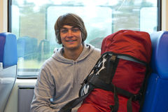 Backpacker. smiling into the camera in front of a train window, with his back pack next to him Royalty Free Stock Photos
