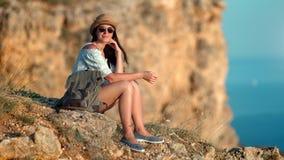 Backpacker atrakcyjna uśmiechnięta kobieta marzy patrzejący pięknego seascape od wierzchołka wysoka faleza zbiory