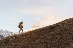 A backpacker in a big fur hat and gloves with a backpack on his back goes uphill against the background of epic cliffs. In the clouds. The concept of mountain Stock Photography