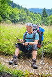 Backpacker checks the route map and navigator sitting on the for Royalty Free Stock Photography