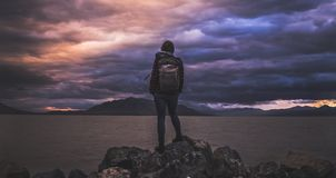 Backpacker on coastline at sunset Stock Photos