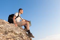 Backpacker con un mapa que mira en la distancia Imagen de archivo libre de regalías