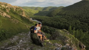 Backpacker couple has a rest in a rock mountains stock video footage