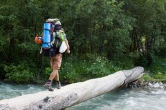 Backpacker crossing the river. Royalty Free Stock Photography