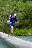 Backpacker crossing the river. Stock Images