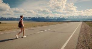 Backpacker de la mujer joven que camina en el camino metrajes