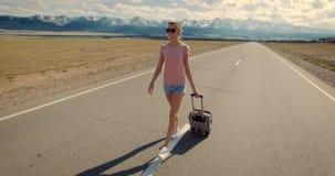 Backpacker de la mujer joven que camina en el camino almacen de video