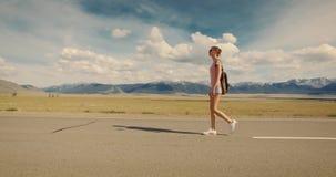 Backpacker de la mujer joven que camina en el camino almacen de metraje de vídeo
