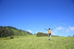 Backpacker de la mujer joven que camina en pico de montaña hermoso Imágenes de archivo libres de regalías