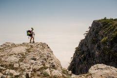 Backpacker de la mujer joven que camina en rastro hermoso del pico de montaña Imagen de archivo