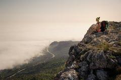 Backpacker de la mujer joven que camina en rastro hermoso del pico de montaña Fotografía de archivo