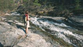 Backpacker de la mujer que camina en la cascada de exploración de la roca en el valle alpino, libertad que hace excursionismo con foto de archivo