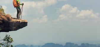 Backpacker de la mujer que camina en el acantilado del pico de montaña imagenes de archivo