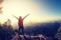 Backpacker de la mujer que camina en el acantilado del pico de montaña de la salida del sol imágenes de archivo libres de regalías