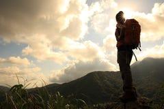 Backpacker de la mujer que camina en pico de montaña foto de archivo