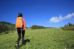 Backpacker de la mujer que camina en pico de montaña hermoso Fotografía de archivo