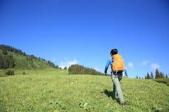 Backpacker de la mujer que camina en pico de montaña hermoso Imagen de archivo libre de regalías