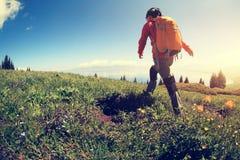 Backpacker de la mujer que camina en pico de montaña hermoso Imagenes de archivo