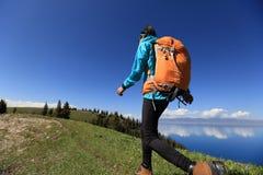 Backpacker de la mujer que camina en rastro hermoso del pico de montaña Fotografía de archivo