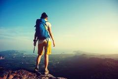 backpacker de la mujer que mira abajo en roca del top de la montaña Foto de archivo libre de regalías