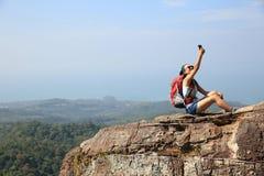 Backpacker de la mujer que toma la foto con el teléfono móvil en pico de montaña foto de archivo libre de regalías