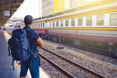 Backpacker de los hombres que espera su tren en el ferrocarril foto de archivo libre de regalías