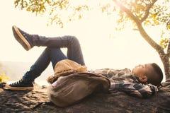 Backpacker del muchacho que duerme en la roca en naturaleza Imágenes de archivo libres de regalías