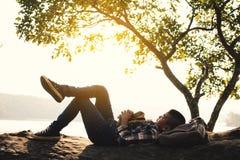 Backpacker del muchacho que duerme en la roca en naturaleza Foto de archivo libre de regalías