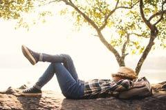 Backpacker del muchacho que duerme en la roca en naturaleza Imagen de archivo libre de regalías