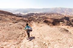 Backpacker descending  hiking mountain ridge stone desert landscape. Backpacker tourist woman mountaineer walking hiking descending mountain ridge stone desert Stock Photography