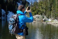 Backpacker die foto met smartphone nemen stock afbeeldingen