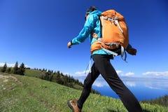 Backpacker die op mooie bergpiek wandelen Stock Foto