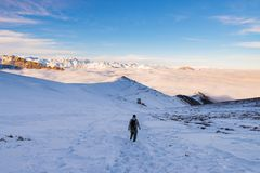 Backpacker die op sneeuw op de Alpen wandelen Achtermening, de winterlevensstijl, koud gevoel, majestueus berglandschap Stock Foto