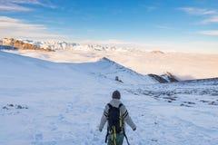 Backpacker die op sneeuw op de Alpen wandelen Achtermening, de winterlevensstijl, koud gevoel, majestueus berglandschap royalty-vrije stock foto's