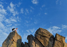 Backpacker on a distant rocky mountain peak Royalty Free Stock Photography